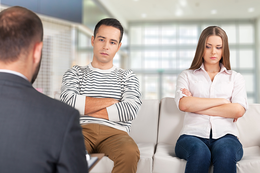 Couple with arms crossed sitting across from a counselor or lawyer
