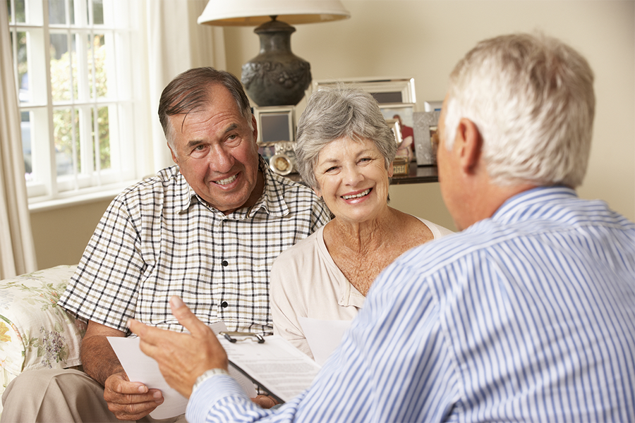 Photo of retired senior couple sitting at home in their living room speaking with a business professional