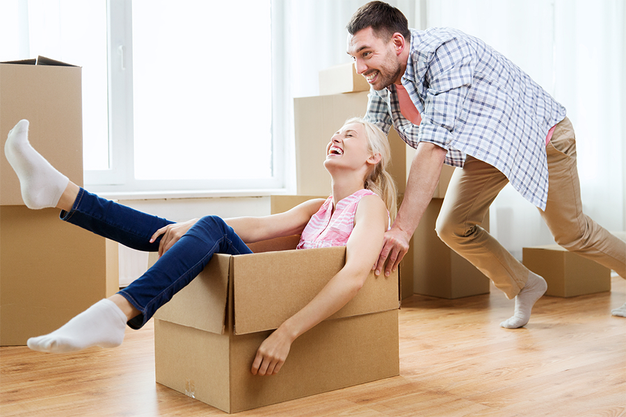 photo of a woman sitting in a box and a man pushing her across a hardwood floor with moving boxes in the background
