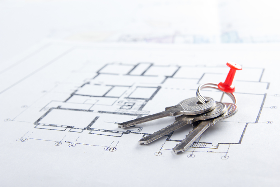 photo of keys on a key ring pinned with a thumb tack on top of property plans