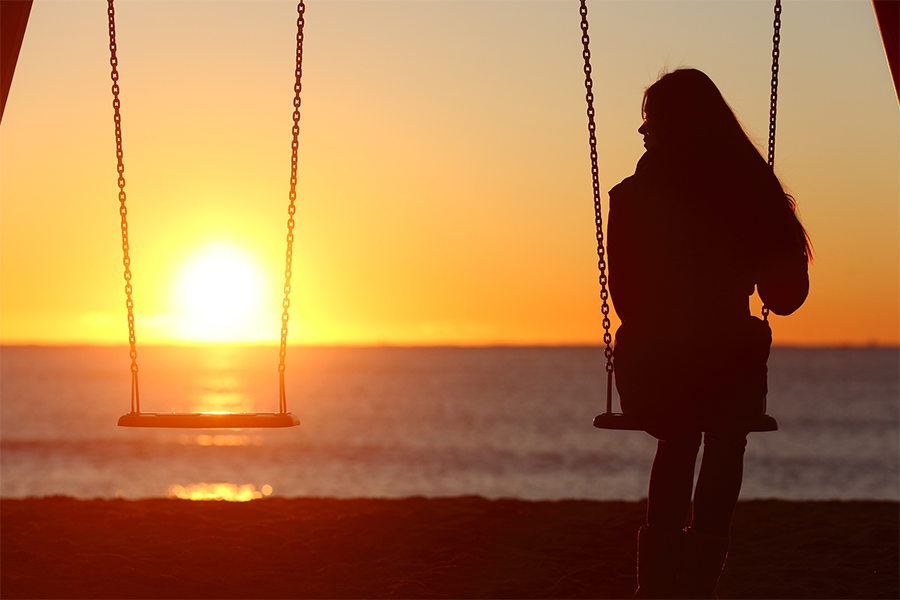 sunset photo of a woman silhouetted on a single swing
