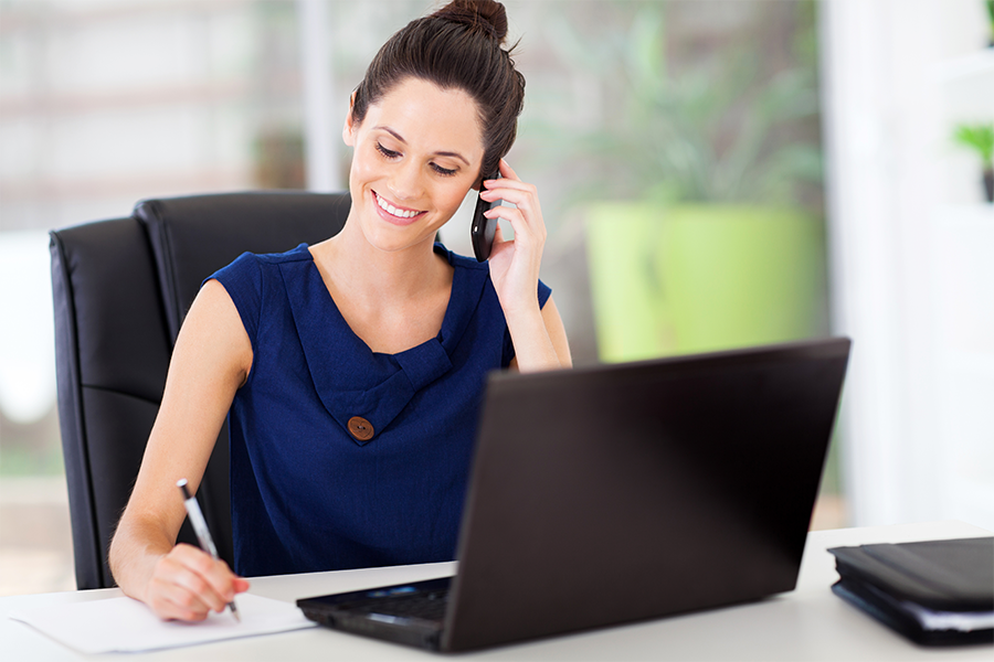 Woman in front of a laptop on the phone smiling and writing down information
