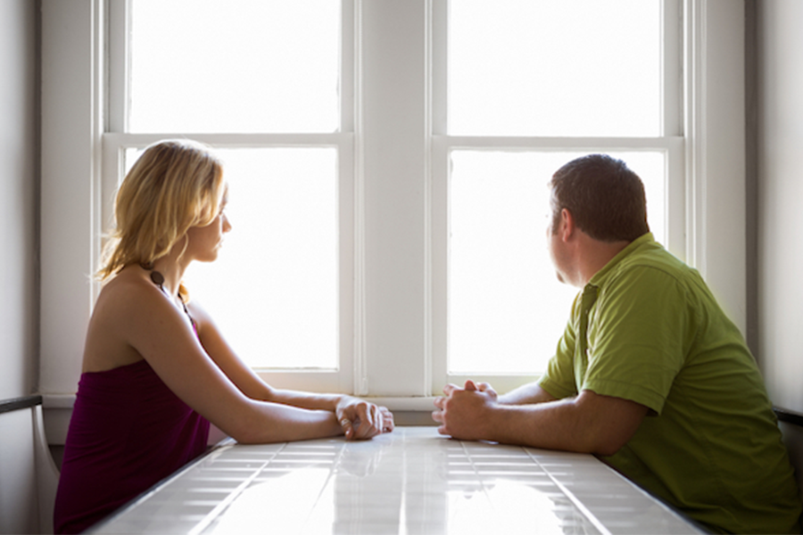 Photo of two people sitting on opposite sides of a table looking out a window