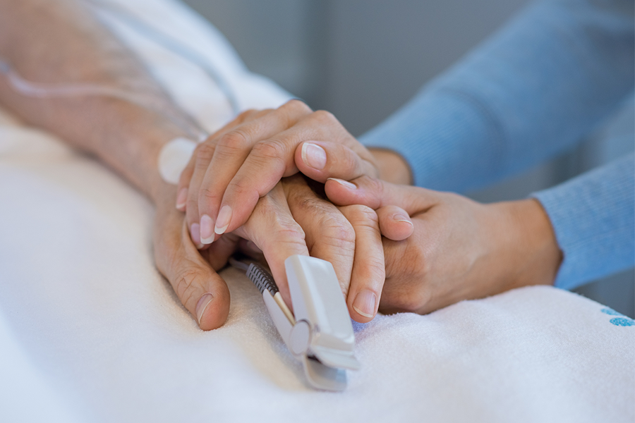 close up of woman holding the hand of someone in the hospital with an oxygen sensor on their hand