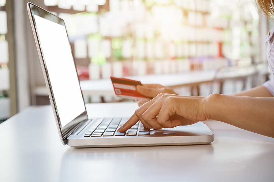 Photo of someone holding a credit card and entering information into a laptop