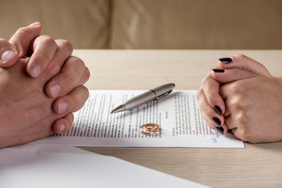 close up of two people's hands folded separately with 2 rings and a pen on paperwork between them
