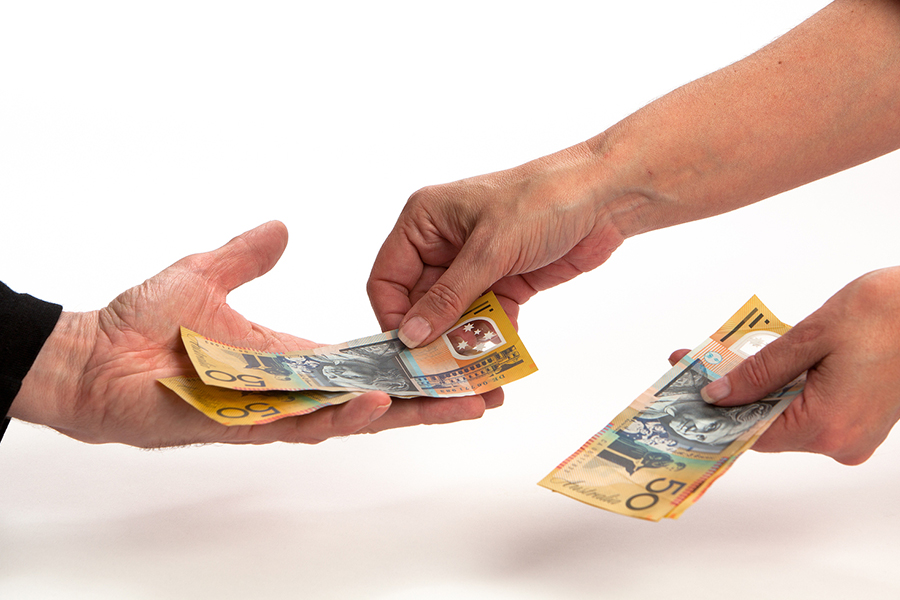 photo of 2 hands, one person handing money to the other (debt collection)