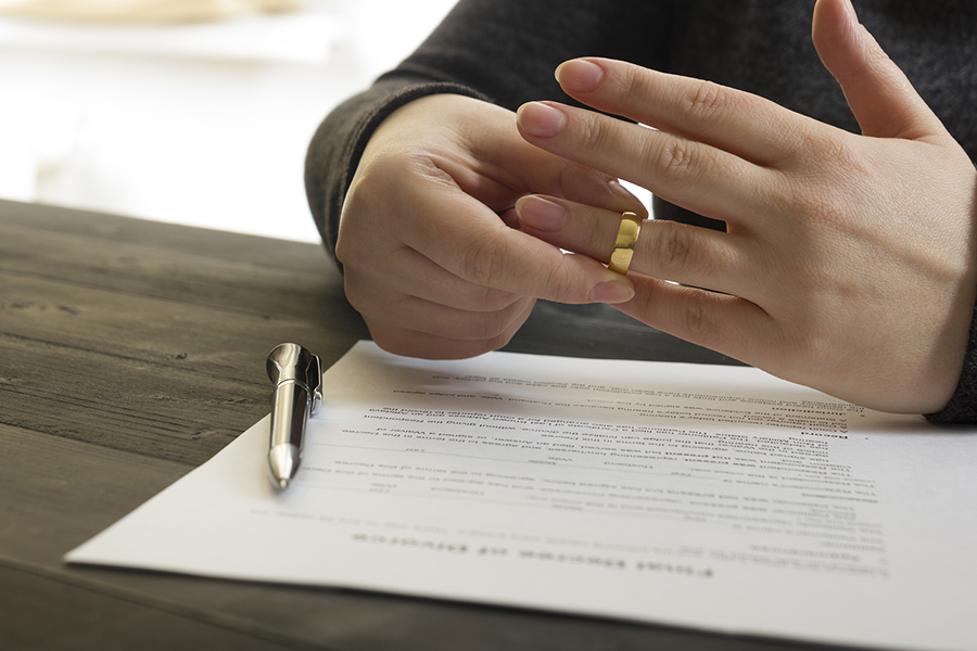 close up of person taking off wedding band over signed paperwork