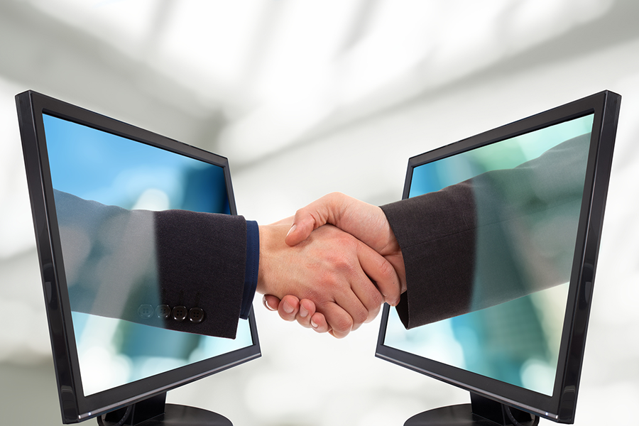 2 computer monitors facing each other with hands reaching out of the screen to shake hands
