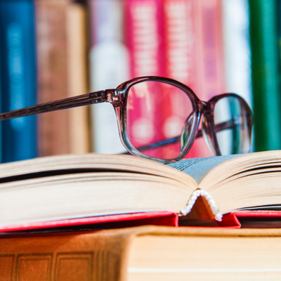 Photo of glasses sat on top of an open book with a book shelf in the background