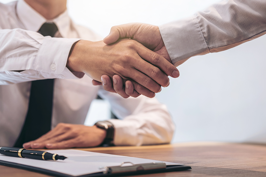 Photo of 2 people shaking hands over signed paperwork on a table