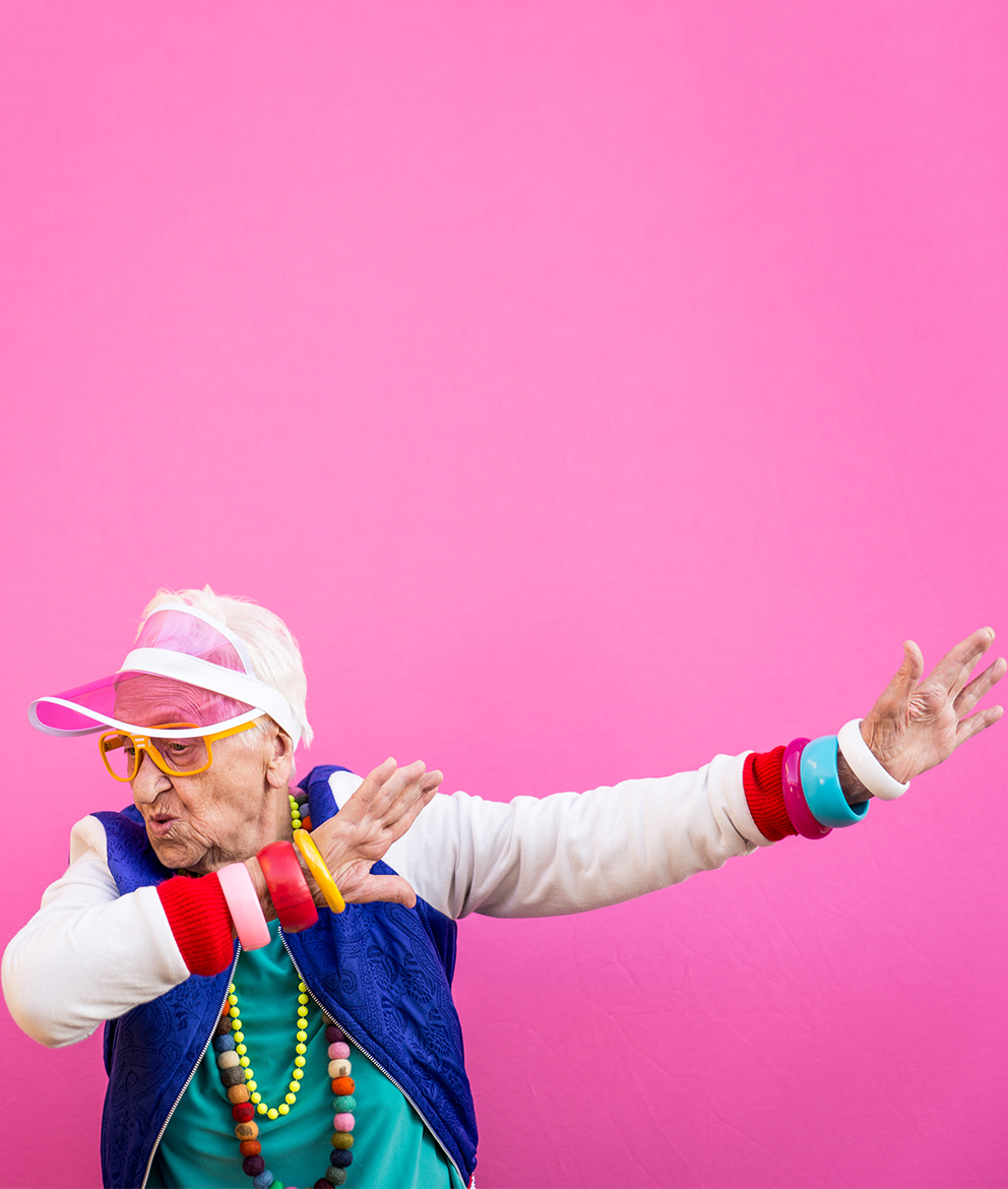 Image of elderly person in colorful clothing on a pink background